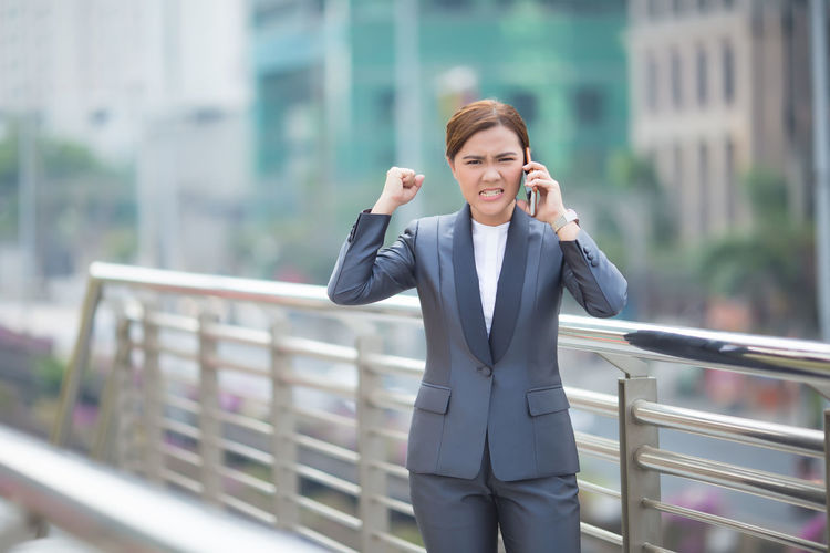 Angry businesswoman talking on mobile phone on bridge in city
