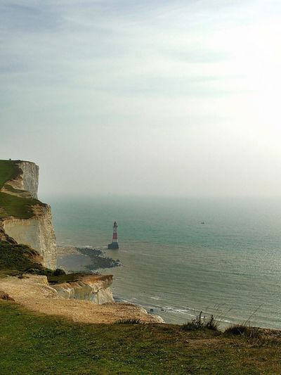 Solitude. Sea Sky Horizon Over Water Water Nature Tranquility Beauty In Nature Outdoors Lighthouse Scenics Ocean England Coast Cliffs Tranquil Scene Built Structure No People Travel Explore Europe Calm Day Grass Beach Cultures