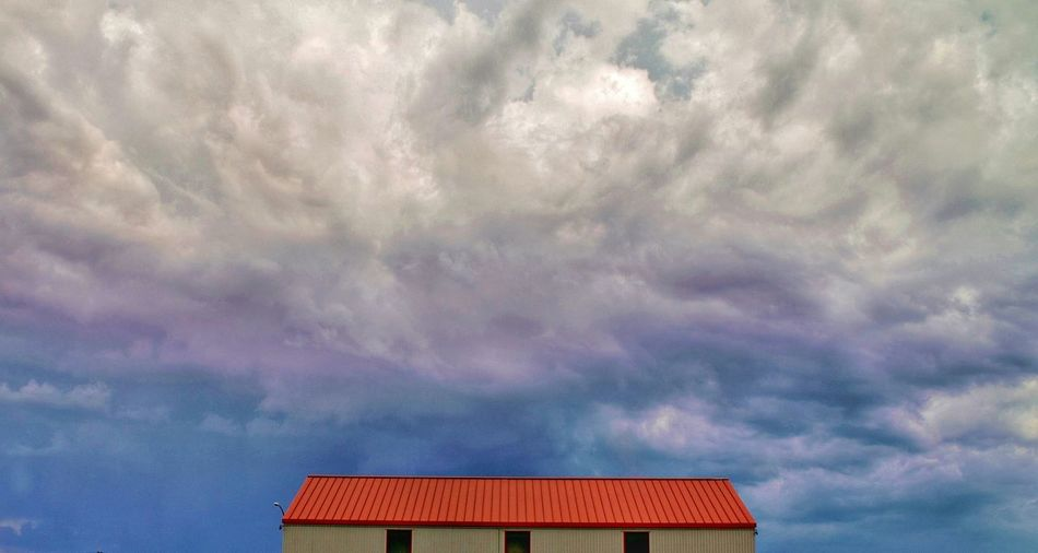 Low Angle View Of Cottage Roof Against Cloudy Sky