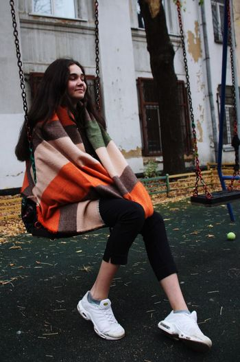 Teenage Girl Sitting On Swing Against Old Building
