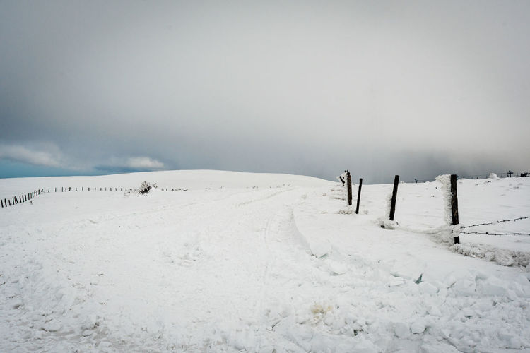 Scenic view of snow covered field against sky