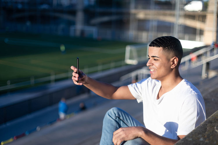 Young man holding camera while sitting outdoors