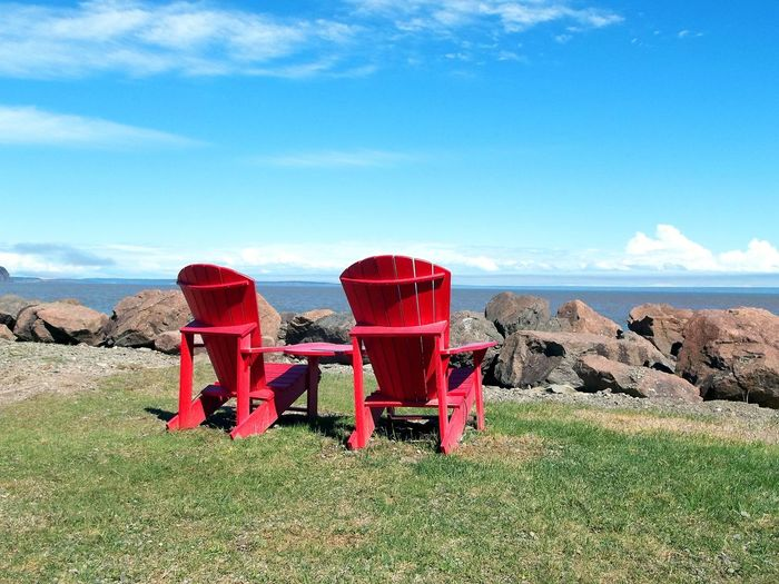 Red chair on landscape against sky