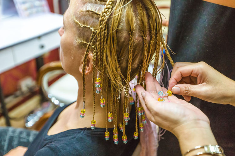 Cropped Hands Of Beautician Holding Beads By Woman Sitting At Salon