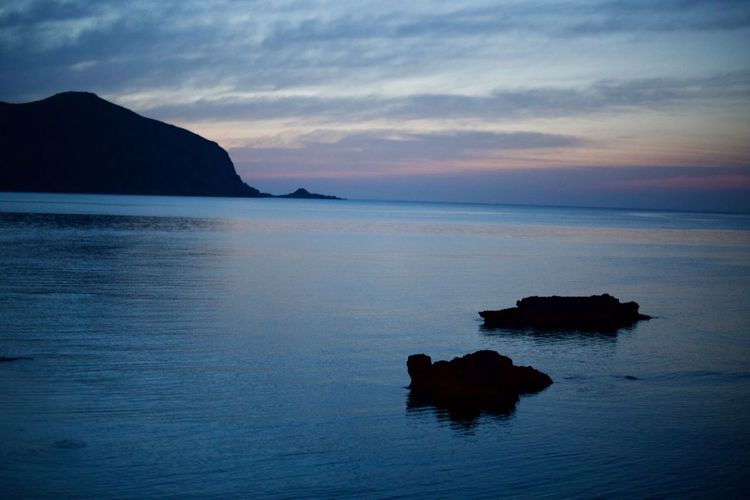 Silhouette rocks in sea against sky at sunset