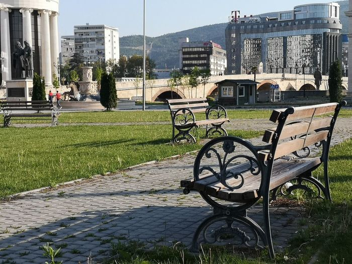 Empty bench by footpath against buildings in city