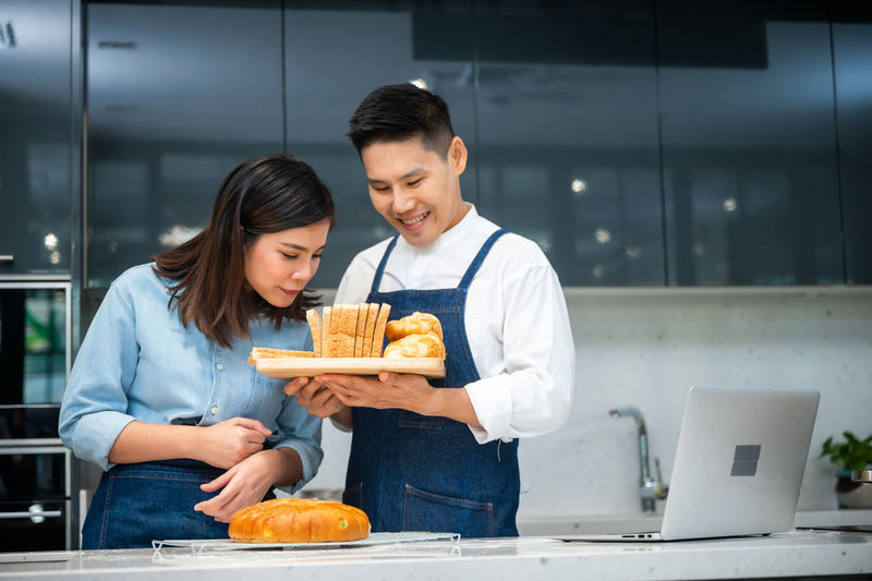 Young man and woman standing in kitchen