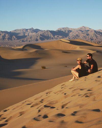 Couple sitting on sand dune in desert against sky