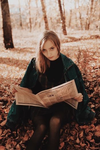 Portrait Of Young Woman Holding Newspaper While Sitting On Field During Autumn