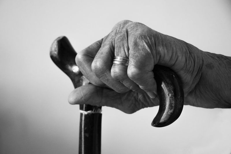 Cropped hand holding walking cane