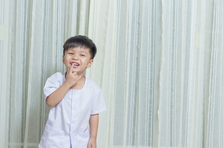 Cheerful Boy Standing Against Curtain At Home