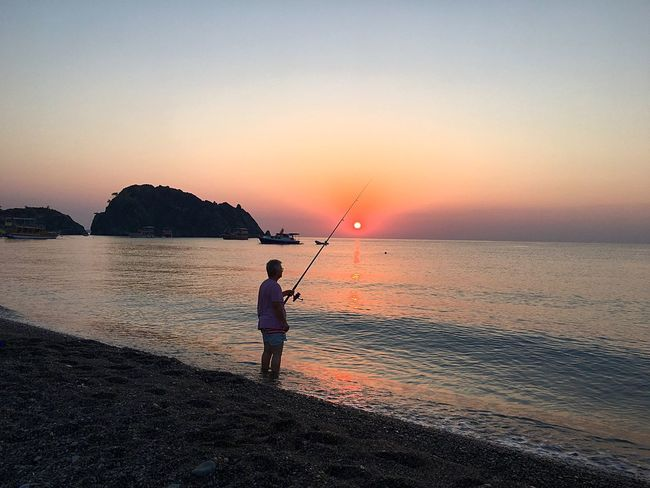 Sunset Sea Full Length Horizon Over Water Tranquil Scene Silhouette Beach Beauty In Nature Water Tranquility Fishing Nature Sun Sky Vacations Outdoors One Person Real People