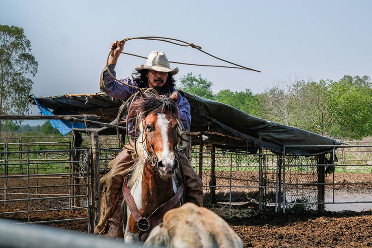 Man riding horse in ranch against clear sky