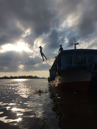 Man jumping over sea against sky