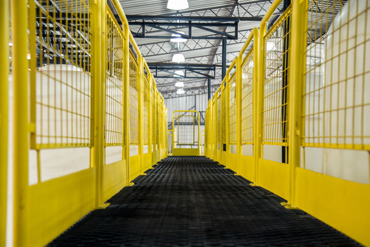 Absence Aisle Architecture Building Built Structure Ceiling Day Diminishing Perspective Direction Domestic Room Empty Factory In A Row Indoors  Industry Metal No People The Way Forward Transportation Warehouse Yellow