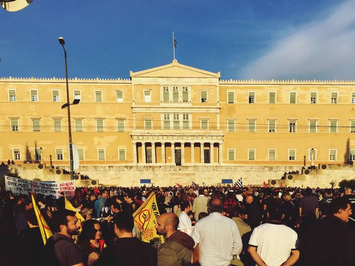 Crowd protesting at greek parliament building against sky