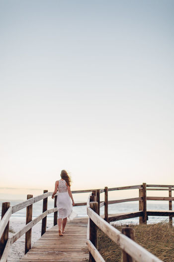 Rea view of young woman walking on pier at beach against clear sky during sunset