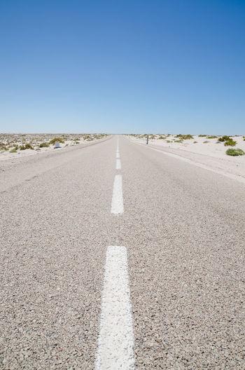 Empty Road Through Sahara Desert Against Clear Blue Sky, Western Sahara, Africa