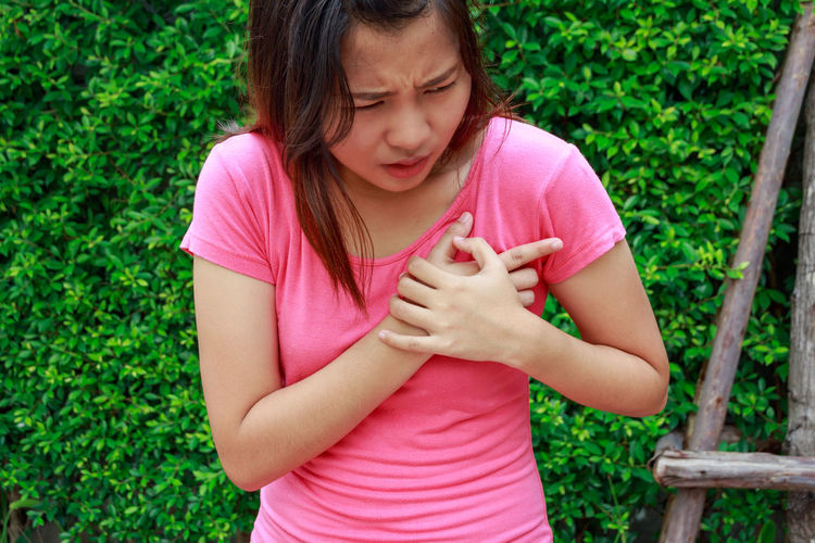 Midsection of woman with chest pain standing outdoors