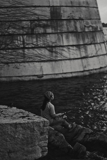 Side view of woman sitting on rock against lake