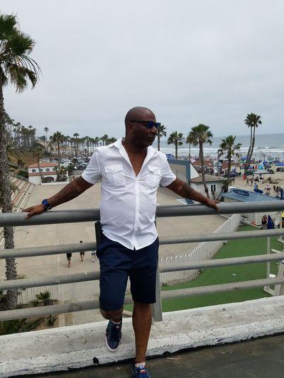 Mature Man Wearing Sunglasses Standing By Railing Against Beach