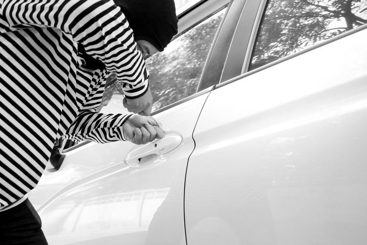 Black and white picture of the man robber with a balaclava on his head trying to break into the car/Selective focus/Criminal and car thief concept Balaclava Black And White Photography Break Into Woods Car Car Thief Casual Clothing Criminal Day Holding Land Vehicle Leisure Activity Lifestyles Men Midsection Mode Of Transportation Motor Vehicle One Person Outdoors Real People Robber Standing Striped Transportation Water Window