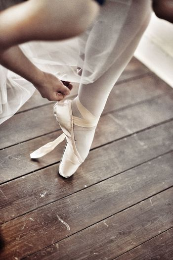 Low section of ballet dancer on floorboard