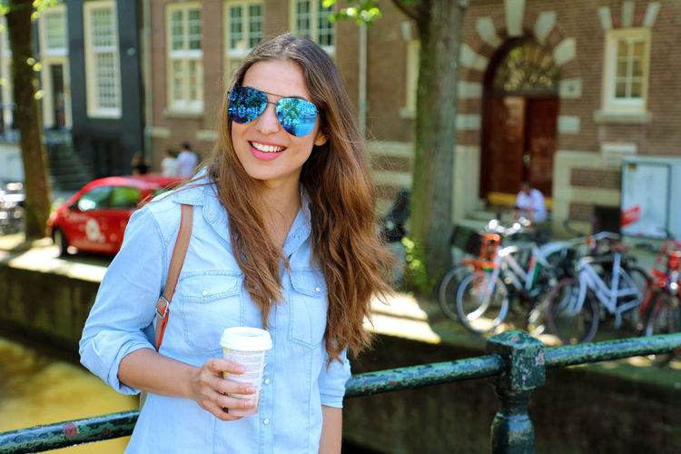 Young woman wearing sunglasses and holding disposable cup of coffee