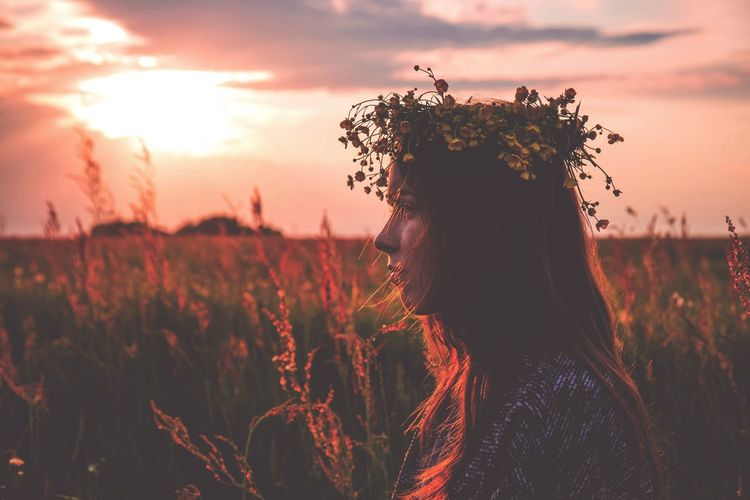 Side view of woman wearing tiara on head at field during sunset