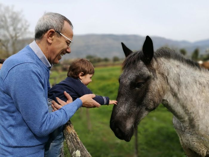 Side View Of Happy Grandfather Assisting Grandson In Touching Horse At Farm