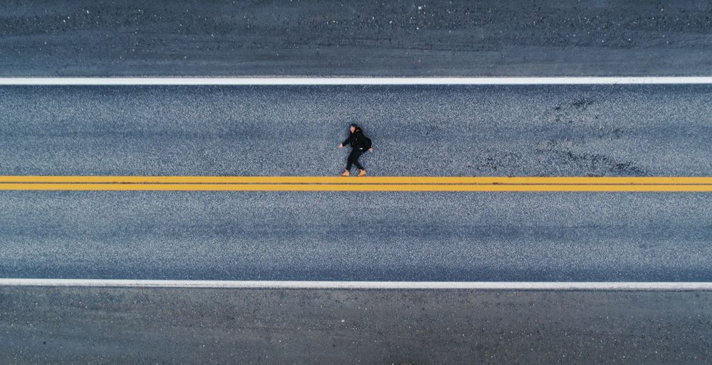 Drone shot of man lying on a highway