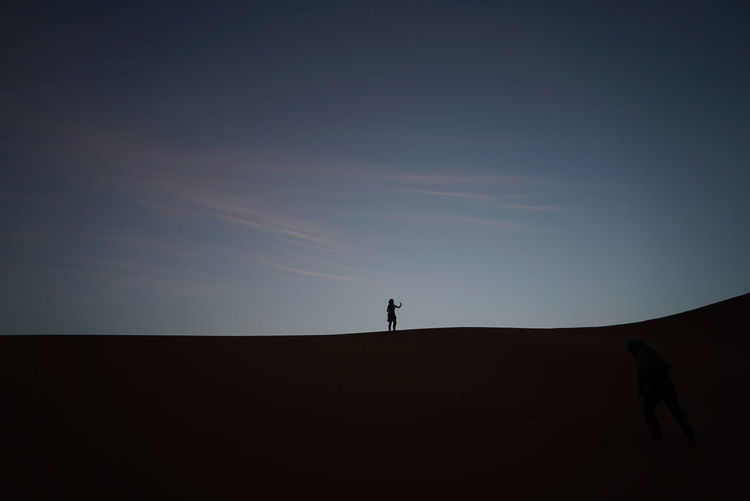 Silhouette of woman walking in sahara desert against sky