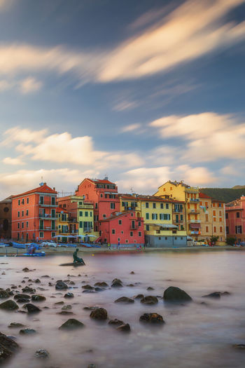 Houses By Sea And Buildings Against Sky During Sunset