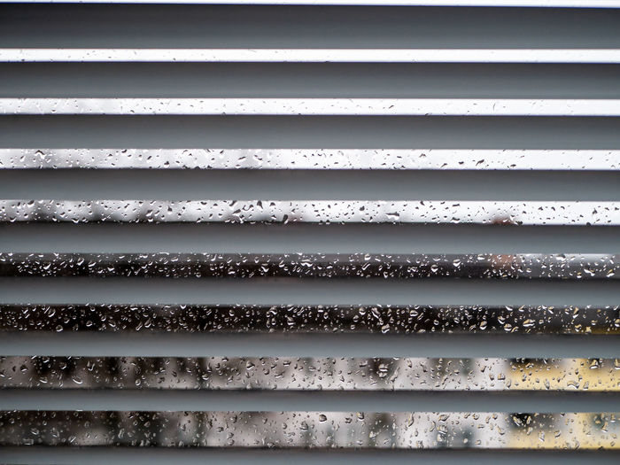 Rainy weather: Wet window with raindrops and grey sky, houses out of focus in background Backgrounds Full Frame Pattern No People Close-up Day Metal Textured  Architecture Wall - Building Feature Outdoors Corrugated Iron Built Structure Repetition Window Blinds White Color Sunlight Iron Corrugated