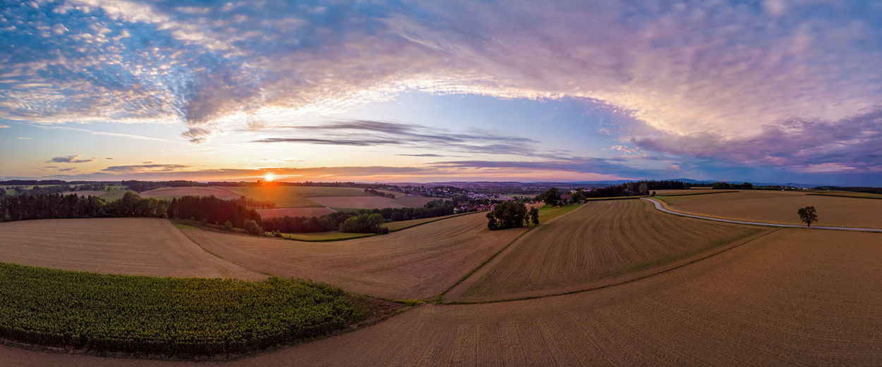 Panoramic view of agricultural field against sky during sunset