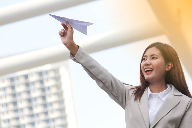 Cheerful businesswoman playing with paper airplane