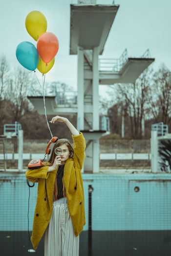 Portrait of woman holding balloons and telephone with magnifying glass outdoors