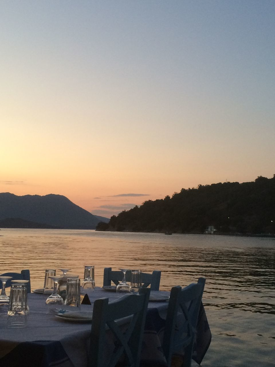 Place Setting By River Against Clear Sky During Sunset