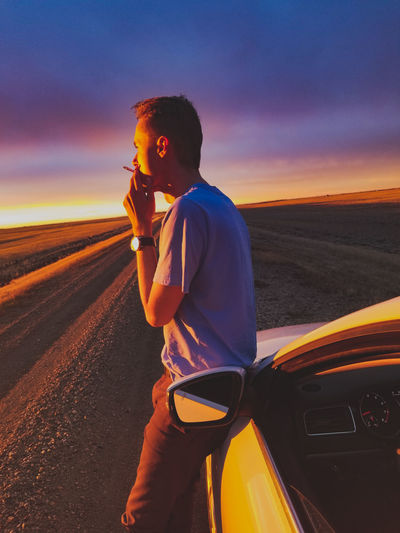 Side view of man smoking cigarette while standing by car on road against sky during sunset