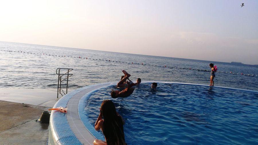 People enjoying at swimming pool by sea