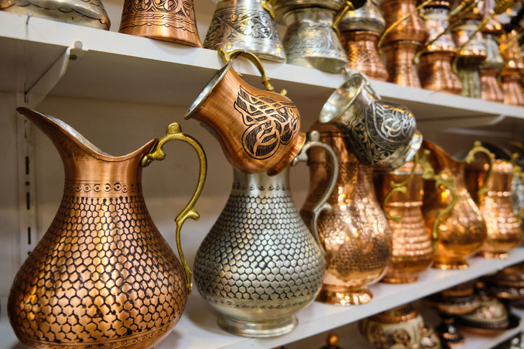 Lots of copper handmade jugs and cezves at shelf of a traditional middle-eastern souvenir store