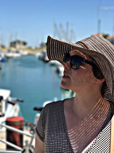 Close-up of woman in sunglasses against boat sailing in sea