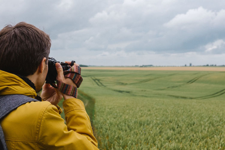 Man photographing agricultural field against sky