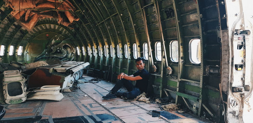 Full length of young man sitting in abandoned airplane