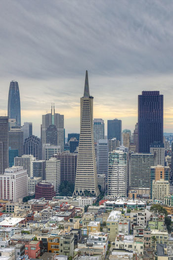 View of buildings in city against cloudy sky