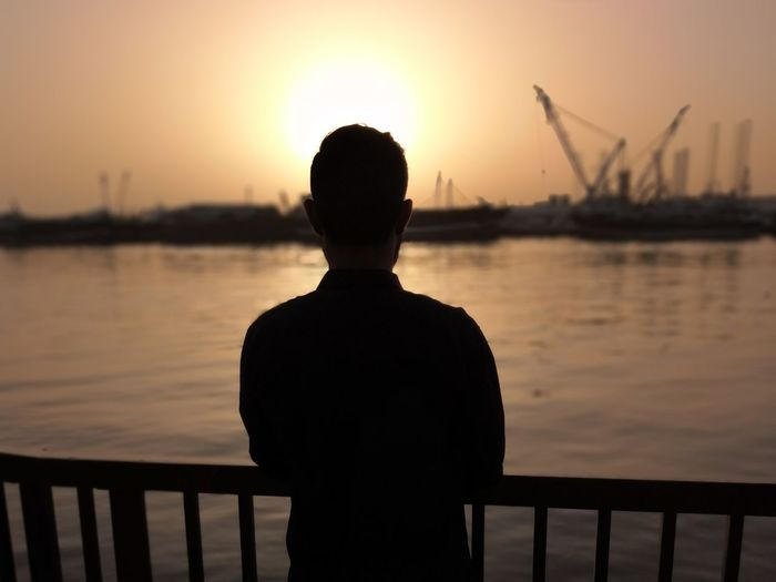 Rear View Of Silhouette Man Standing At Harbor Against Sky During Sunset