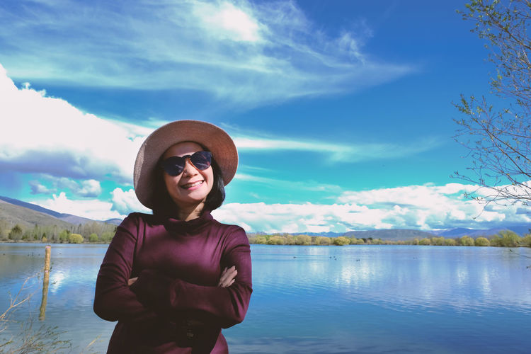 Cloud - Sky One Person Sky Lifestyles Front View Standing Leisure Activity Lake Water Beauty In Nature Hat Scenics - Nature Waist Up Portrait Outdoors Smiling Nature Clothing Adult Blue Lagoon New Zealand Sunny Day Happiness Landscape