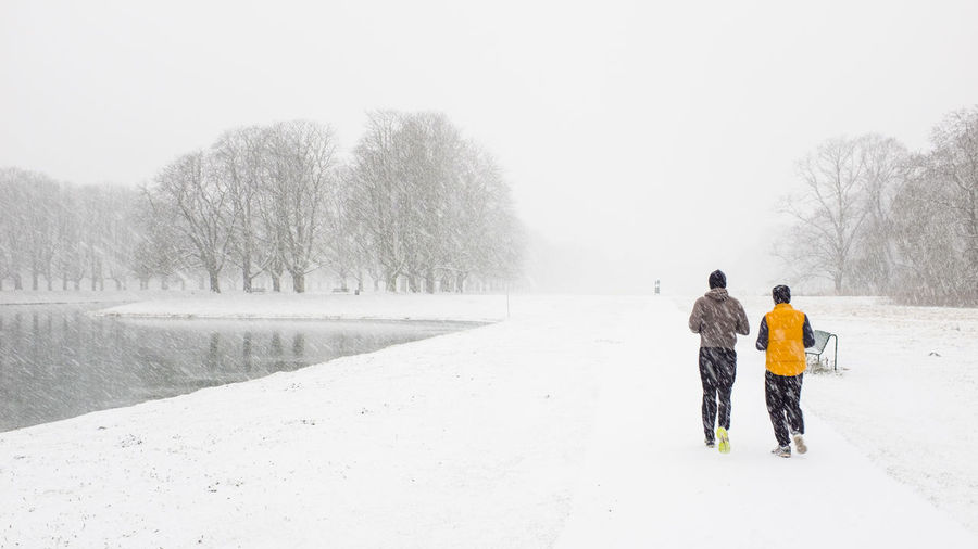 Rear view of people jogging on snow covered landscape