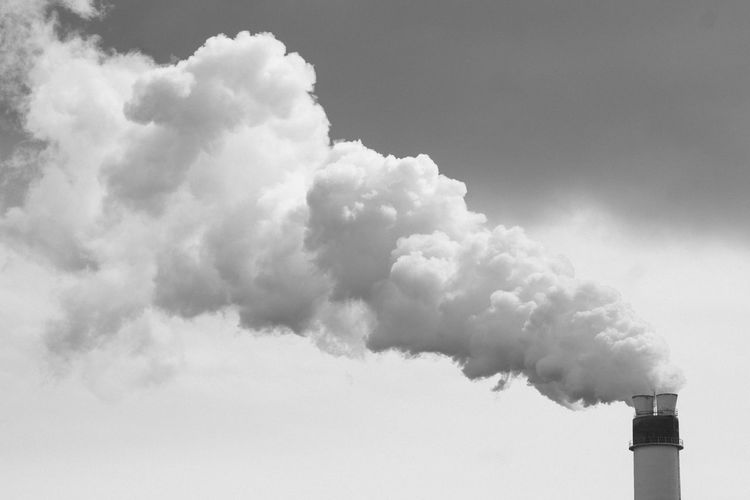 Smoke emitting stack against sky