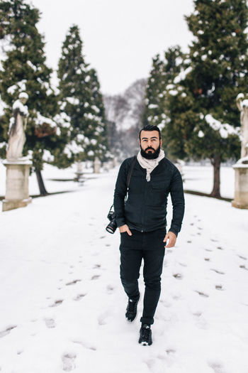Portrait of handsome man with camera on snow covered footpath during winter